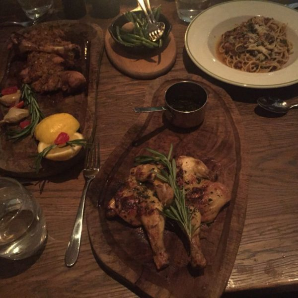 ariel view of wooden board with chicken and side view of lamb chops