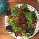 a hand painted plate of Turkish kuru kofte kebabs on a bed of peas surrounded by salad