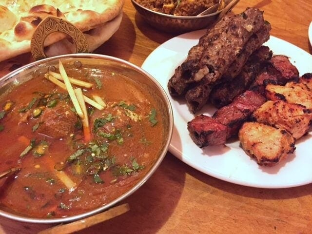 plate of kebabs and karahi gosht in bowl