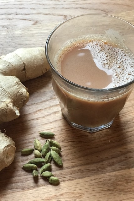 Masala tea in a small glass with ginger and cardamom pods