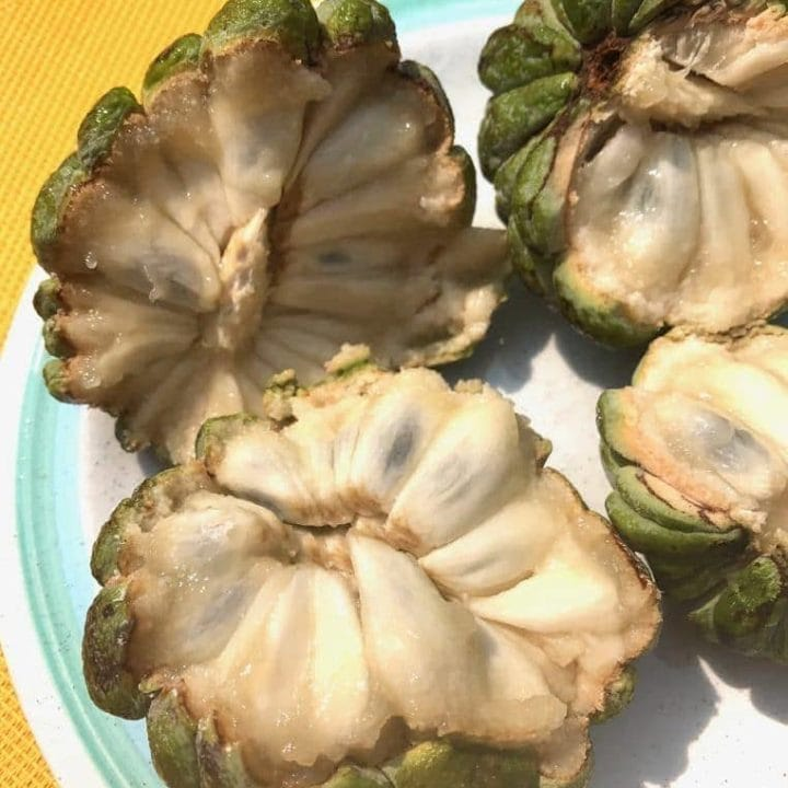 two custard apples cut in half showing inside flesh and seeds