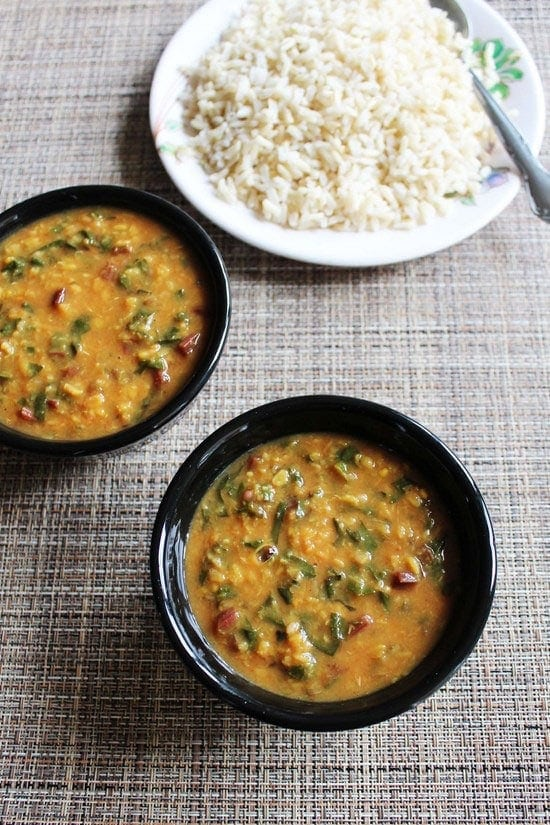 2 bowls of dal next to plate of rice