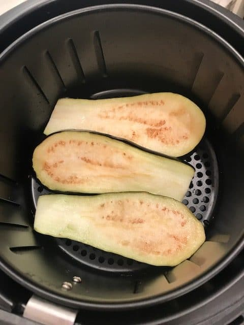 3 slices of raw eggplant lying flat, in the air fryer basket