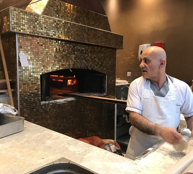Baker preparing lahmacun in front of wood fired oven