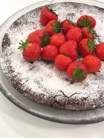 Whole kladdkaka with a hand-full of strawberries on top