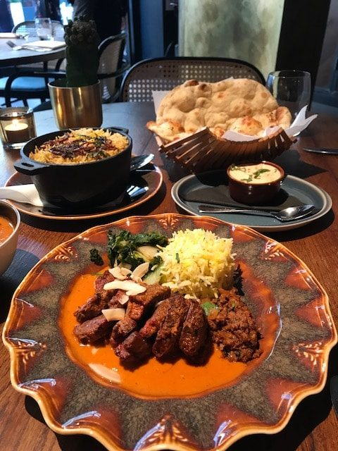 lamb rump, biryani, raita and naan on table