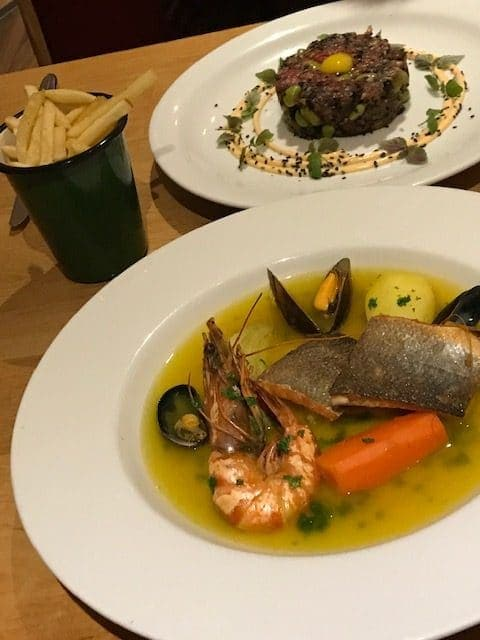 front dish of seafood bouillabaisse, serving of fries and a dish of beef tartare