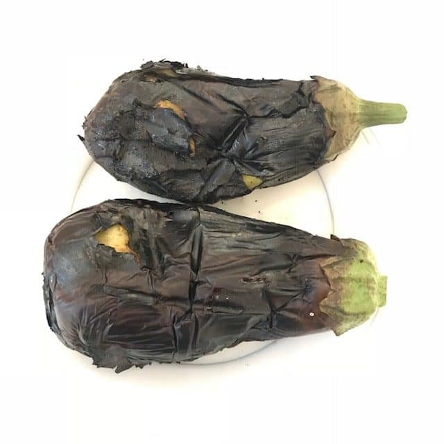 two roasted eggplants on a plate