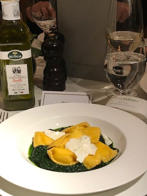 plate of ravioli on black kale sauce next to a bottle of Novello olive oil