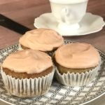 three cupcakes on a small plate next to 2 white coffee cups on saucers