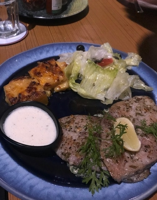 Grilled kingfish steak on a blue plate with salad
