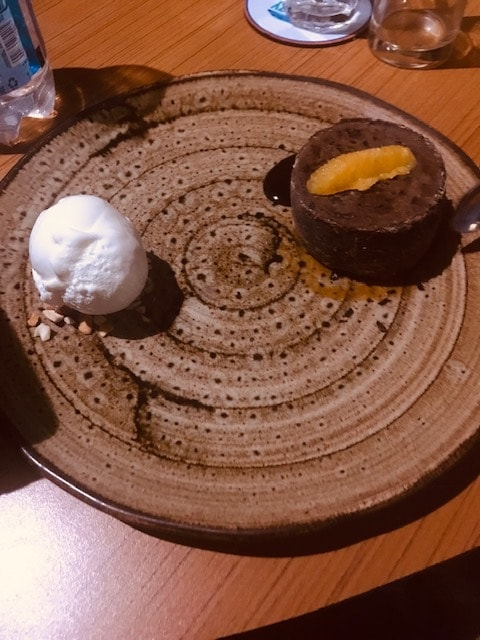 chocolate cake with vanilla ice cream on a brown plate
