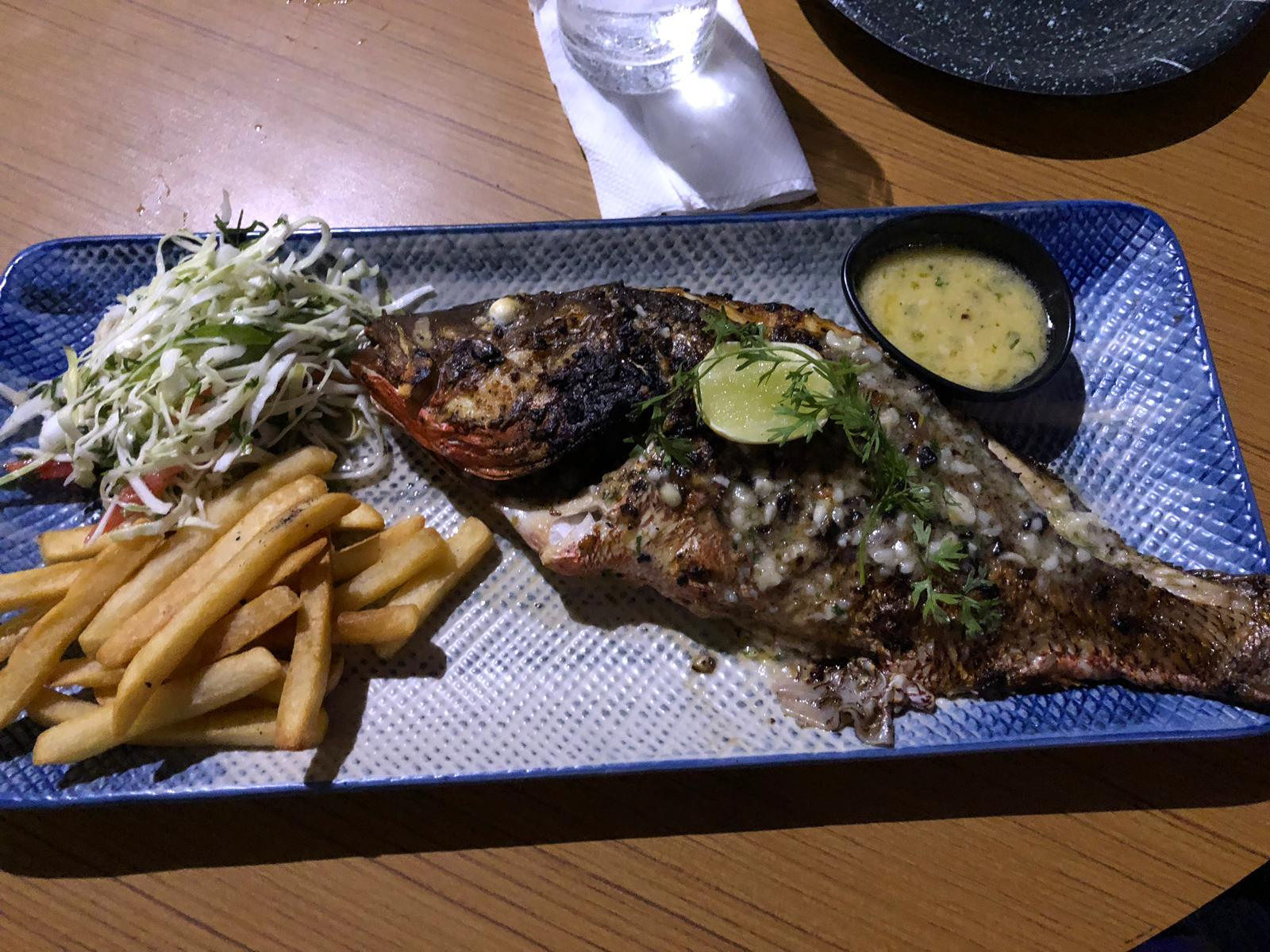 blue platter with a whole grilled seabass, salad and fries