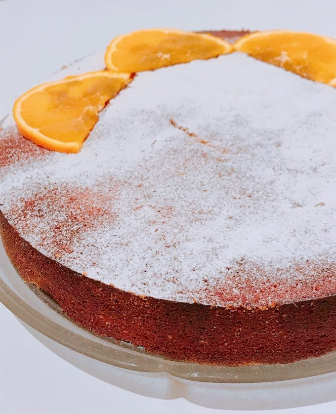 Orange & almond cake with slices of orange and dusting of sugar