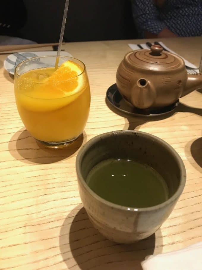glass of orange juice and cup of matcha tea