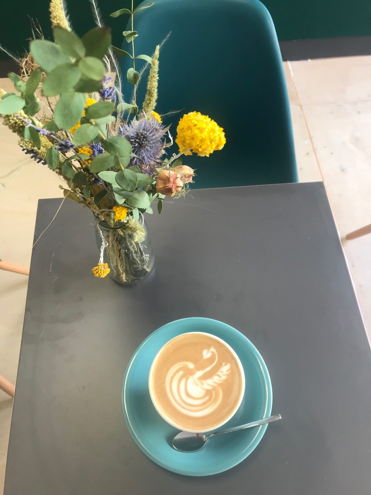 dried flowers and a cup of coffee on a table