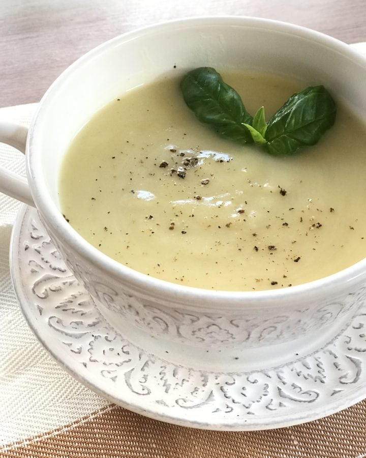 soup in a white bowl, garnish with basil leaves