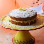 Image of banana cake with slice of lemon and sprinkles on a cake stand.